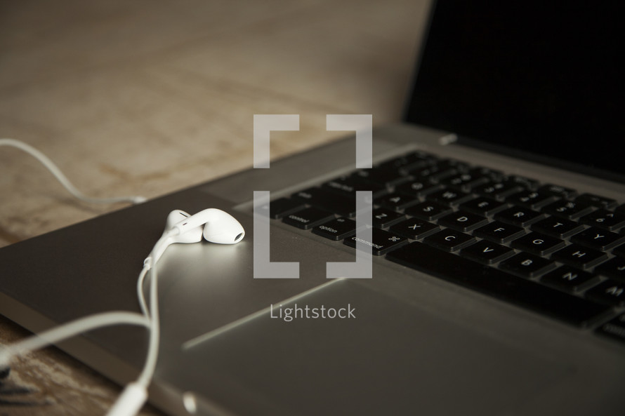 earbuds on a laptop