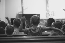 children singing and making hand motions to worship songs