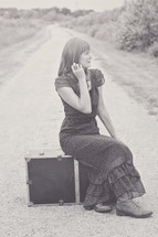 woman sitting on a suitcase on a dirt road
