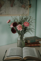 vase of red and pink flowers and an opened Bible
