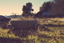 An old couch in a field outdoors.