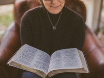 Woman reading the Bible while sitting in a chair.