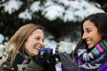 women with mugs in the snow