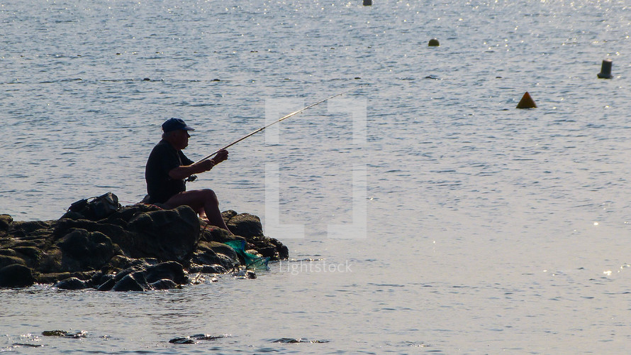 a man fishing at the ocean sitting on rocks