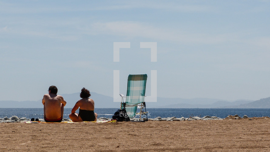man and a woman sitting on a beach