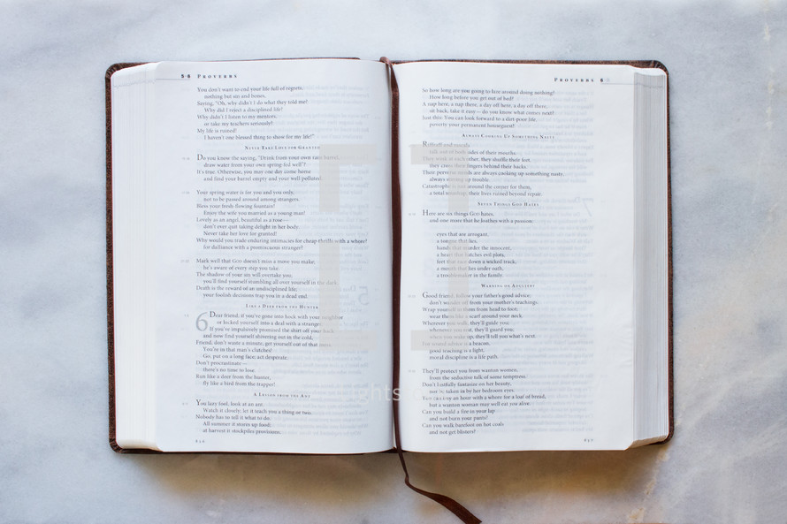 A bible turned to Proverbs on a white marble counter top