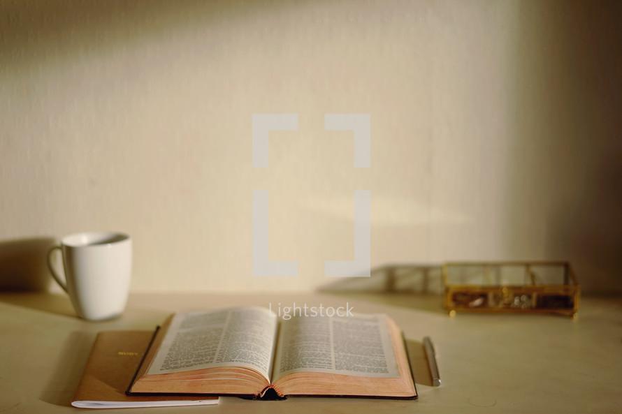 open Bible, coffee mug, journal, pen, and basket on a desk