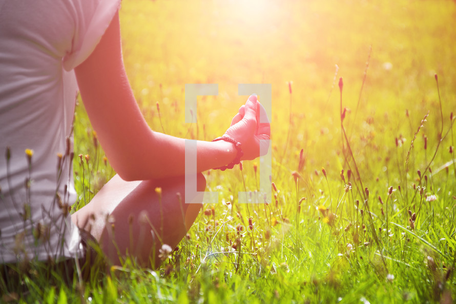 a woman mediating in the grass