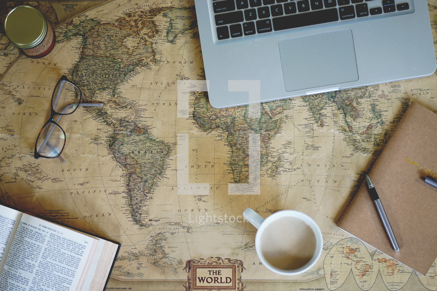 open Bible, mug, reading glasses, laptop,  pen, journal, and ink on a world map