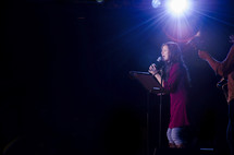 Female worship leader leading worship in a contemporary worship service