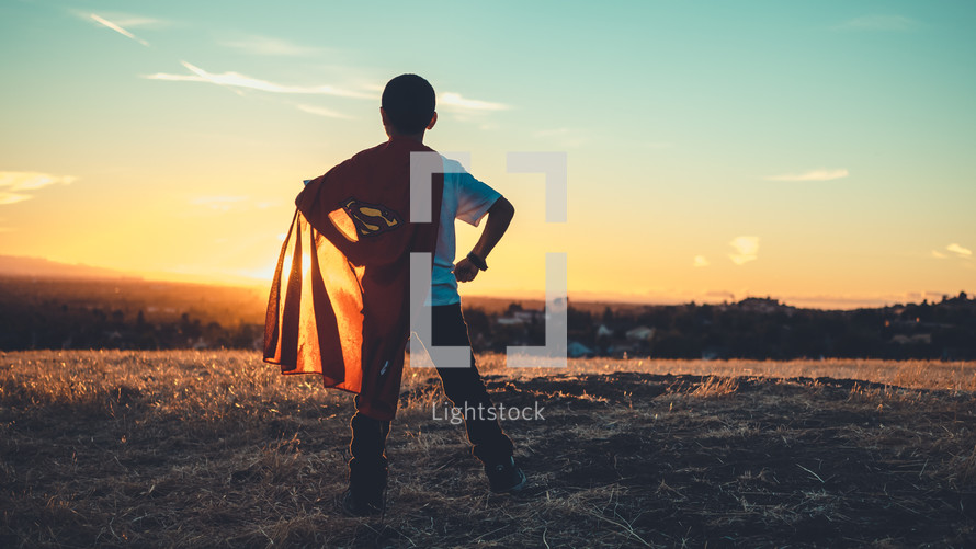 Boy facing the sun, wearing a superman cape, looking determined. Imagination | Dreaming | Destiny | Vision| Heroes | Justice | Kids Ministry | Movies | Heroes | Bravery | Brave | Courage | Courageous | Strong | Strength | Stand | Determination | Persevere | Sermon Series |