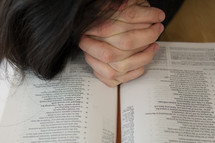 a woman with praying hands over the pages of a Bible