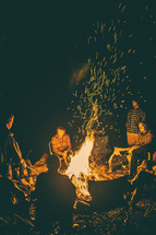 people sitting around a campfire at night