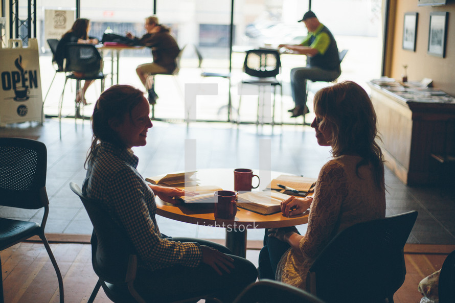 Two women in a coffee shop, visiting, studying their bibles, drinking coffee