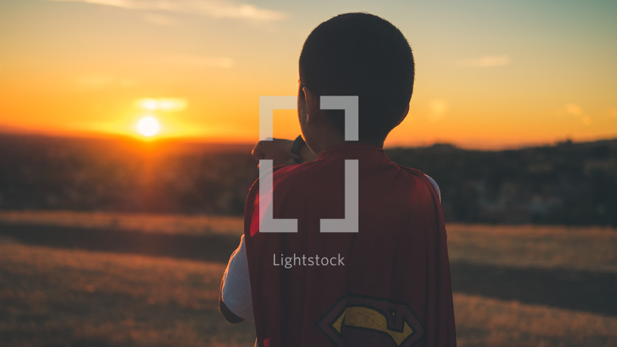 Boy facing the sun wearing a superman cape. Imagination | Dreaming | Destiny | Vision| Heroes | Justice | Kids Ministry | Movies | Heroes | Bravery | Brave | Courage | Courageous | Strong | Strength | Stand | Determination | Persevere | Sermon Series |