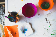 paintbrushes and paint on a table