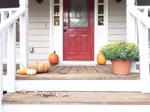 pumpkins and mums on a front porch