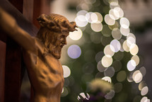 bokeh lights from a Christmas tree and crucifix in a church