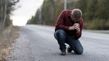 a man kneeling in prayer in the middle of a rural road