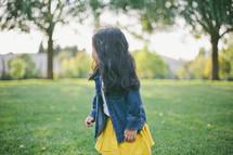 A little girl looking away in a field of grass.