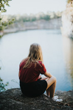 teen girl sitting by the edge of a pond