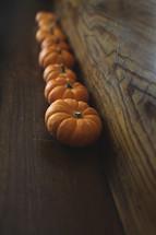 row of orange pumpkins on wood