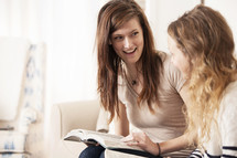 friends reading Bibles together sitting on a couch.