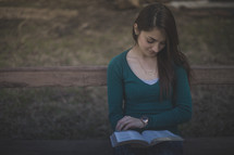 A young woman sitting on a bench reading the Bible