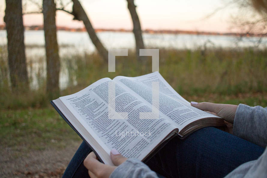 a woman sitting outdoors reading a Bible