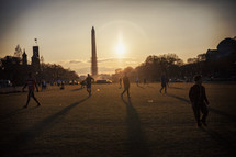 Washington monument at sunset with people walking on the lawn.