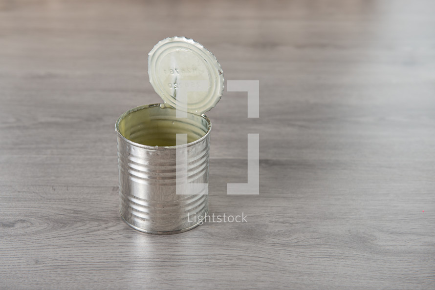 open tin dirty can on a light wooden background