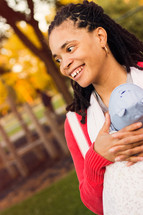 Smiling woman carrying an infant in a baby sling carrier.