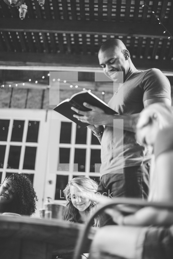 man reading a Bible to a group at a Bible study