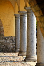 Stone columns in a medieval building with cobbled stone paving