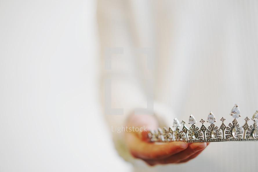 a woman holding a tiara