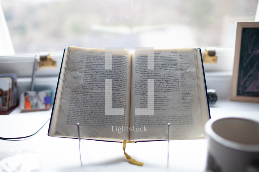 open Bible on a stand in a window on a desk