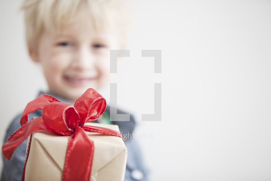 A child holding a wrapped gift.