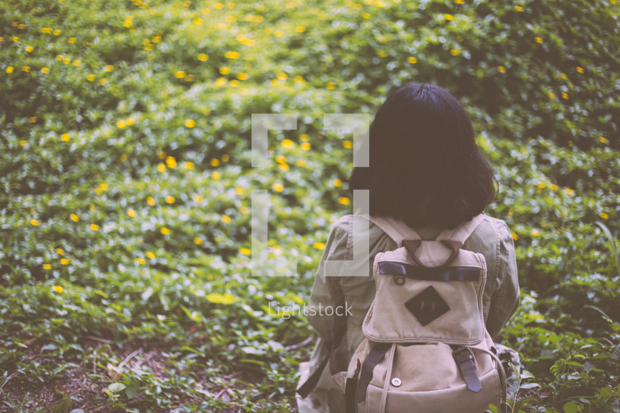 a woman with a backpack standing outdoors