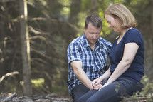 Couple praying together in wooded area and holding hands while sitting on log