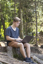 Teenager working on laptop computer in rural wooded environment in woods