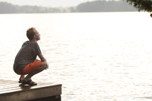 Teenager sitting on dock and praying with head looking up