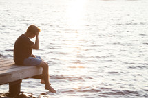 Teenager sitting on dock and praying with head down