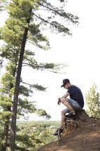 Teenager sitting on stump and praying high up on a cliff area