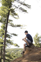 Teenager sitting on stump and praying on high cliff