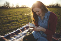 young woman sitting on a blanket in the grass reading a pocket Bible under sunlight