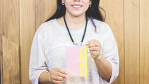 a woman holding up a badge pass