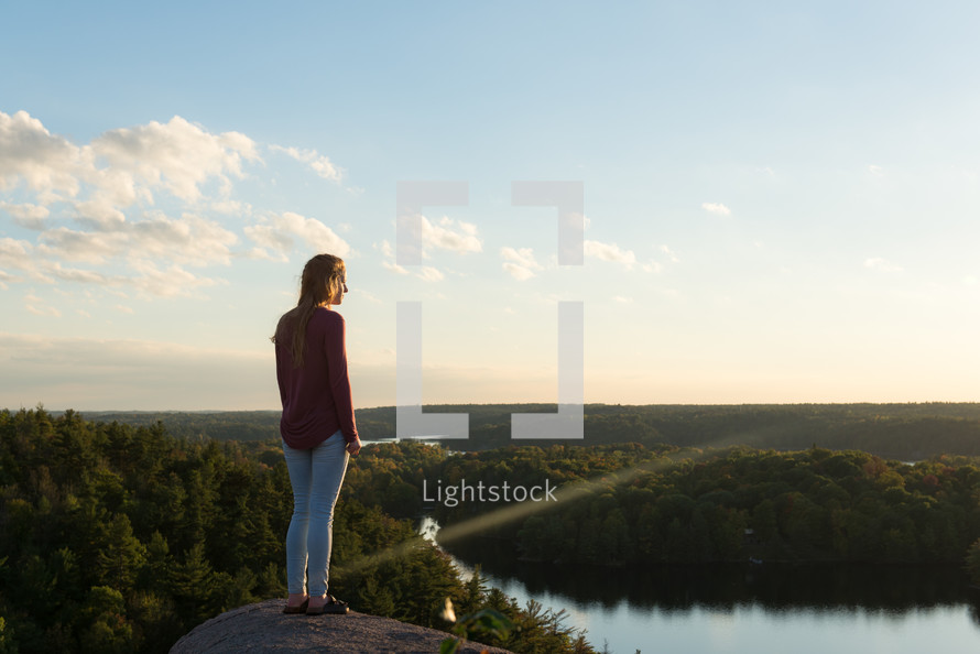 a woman looking down at a lake taking in the view