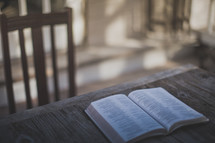 An open Bible sitting on a wooden table