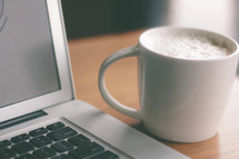 coffee cup and an open laptop