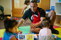 father playing with his toddler daughters in a playroom